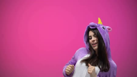 piada : Smiling woman having fun and dancing in funny unicorn pajamas, carnival party