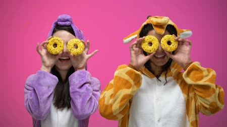piada : Young women in funny pajamas closing eyes with donuts, fooling around, joke