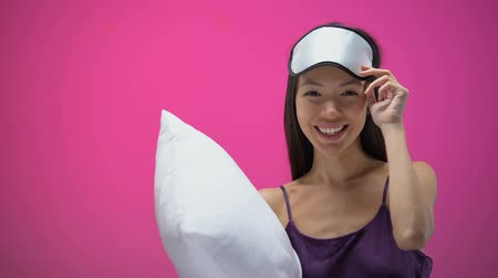 uykulu : Asian lady with pillow showing silence sign and wearing eye mask, ready to sleep Stok Video