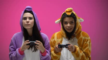 pizsama : Female friends wearing giraffe and unicorn pajamas playing videogame, having fun