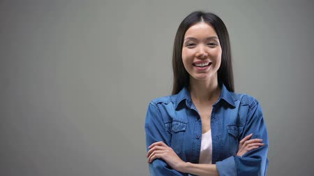Çapraz kollar : Smiling young Asian woman standing with hands crossed and looking on camera Stok Video