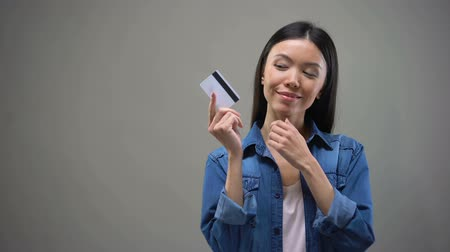 リミット : Smiling Asian woman holding credit card and thinking about shopping, no limits