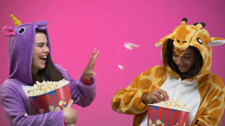 veselí : Female friends in funny pajamas having fun, throwing popcorn to each other