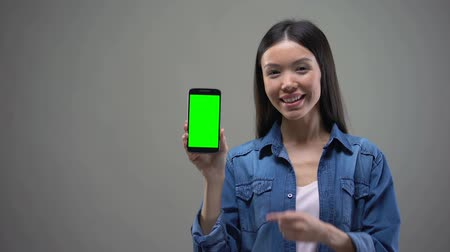 em branco : Happy Asian woman showing smartphone with green screen, online banking, shopping