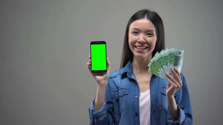 servet : Smiling Asian woman holding smartphone and euros, working online, cash back