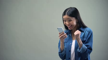 příznivý : Asian lady sincerely rejoicing holding smartphone, favorable tariffs for calls Dostupné videozáznamy