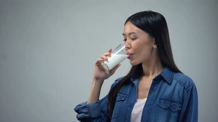 laktóz : Asian lady drinking milk in morning, source of calcium and energy, bifidoproduct Stock mozgókép