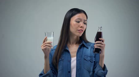 cálcio : Woman trying to chose between unhealthy carbonated drink and useful healthy milk