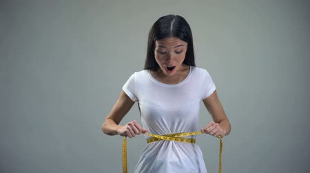 be sad : Obsessed woman tightening measuring tape on her waist desire to be slim, bulimia