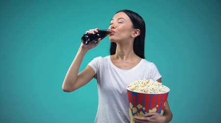 carbonated beverages : Asian woman holding big paper cup with popcorn and drinking soda visiting cinema