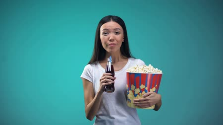 działka : Woman with cup of popcorn sincerely laughing watching comedy and drinking soda