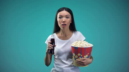 działka : Absorbed in plot of film woman drinking fizzy water and eating popcorn, cinema Wideo