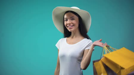 sunhat : Asian woman in sun hat holding big sum of dollars and many shopping bags, loan