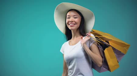 sunhat : Young woman enjoying shopping, holding big sum of euro, crediting system