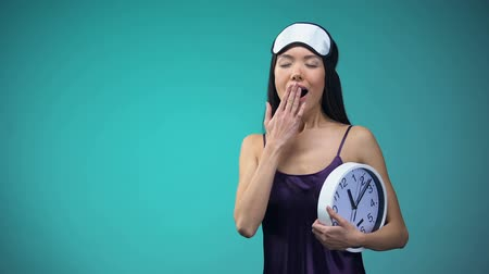 пробуждение : Young woman in pajamas yawning and stretching with clock in hands late awakening