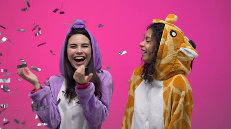 幼稚な : Excited women in funny animals pajamas standing under confetti shower, hugging