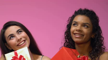 exited : Two multiethnic women holding giftboxes and dreaming about holidays, close up