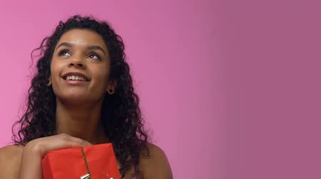 presentes : Afro-American woman holding giftbox and looking up, dreaming about romantic date Stock Footage