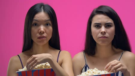 bűbájos : Two women in pajamas eating pop corn and attentively watching interesting movie