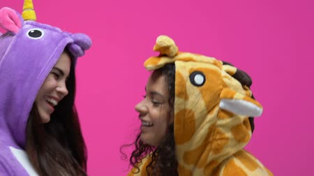 jó hangulatban : Multiethnic women in unicorn and giraffe pajamas hugging and laughing, fun Stock mozgókép