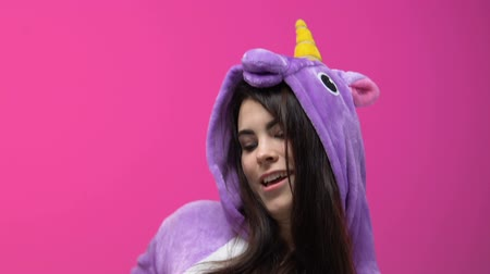 piada : Young lady in unicorn pajamas dancing on carnival party against pink background