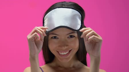 eye mask : Beautiful Asian woman in pajamas and sleeping mask flirting, looking into camera