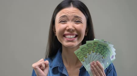 euro banknotes : Excited Asian lady showing bunch of euros to camera, lottery winner, wealth