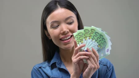 euro banknotes : Pensive Asian woman looking at bunch of euros, thinking about shopping, closeup