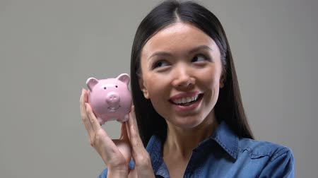 fascinante : Young Asian woman shaking piggy bank, saving money and investment, close up Stock Footage