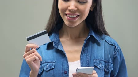 ganhos : Asian lady holding smartphone and credit card, online banking services, shopping