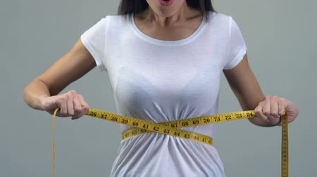anorexia : Asian woman measuring waist with tape-line, happy about weight loss diet concept