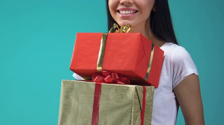 giveaway : Cheerful young lady holding gift boxes, holidays presents for friends and family Stock Footage