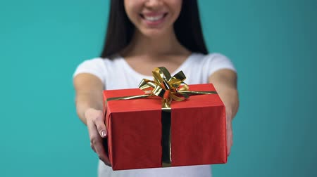 giveaway : Cheerful girl showing gift box to camera, isolated on blue background, holidays Stock Footage