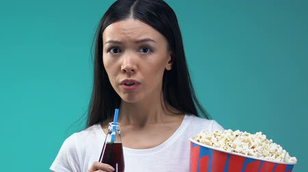 восхитительный : Asian girl with pop corn and sweet beverage watching scary movie, close-up Стоковые видеозаписи