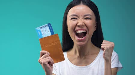 id : Excited Asian lady holding passport and flight tickets, work abroad, emigration