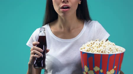 восхитительный : Impressed lady holding pop corn and drinking sweet beverage, watching movie