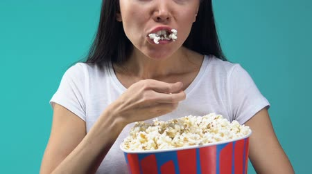 pop corn : Young woman with popcorn attentively watching TV show, overeating, junk food