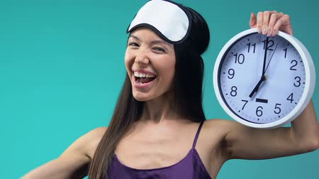 pizsama : Happy Asian woman in pajamas and eyemask showing force and clock morning wake up