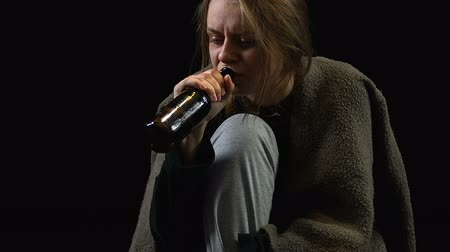 過剰摂取 : Miserable woman drinking alcohol from bottle sitting on floor, addiction, crisis