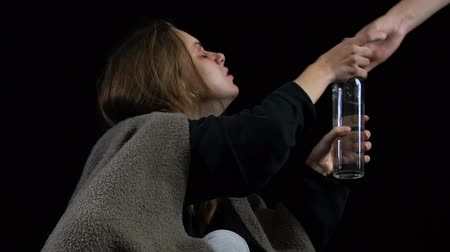 geri çekilme : Hand holding out bottle of alcohol, woman drinking beverage avidly, addiction Stok Video
