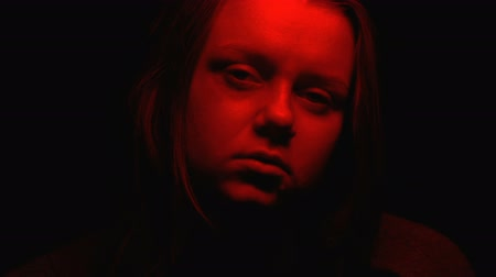 жестокий : Close-up aggressive female face in red light appearing from darkness, nightmares Стоковые видеозаписи