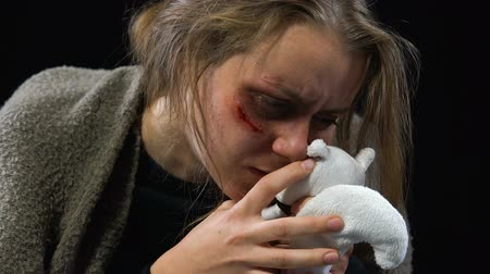 трагедия : Bruised woman hugging toy, victim of kidnapping missing family, physical abuse