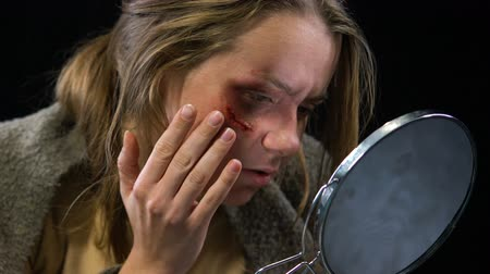batido : Woman looking at wound in mirror, feels desperate to stop domestic violence