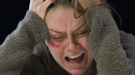 teror : Bruised woman shouting crying, victim of violence suffering from mental disorder