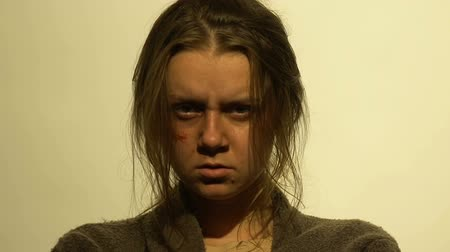 mistreatment : Portrait of beaten disheveled woman, victim of physical abuse, cry for help Stock Footage
