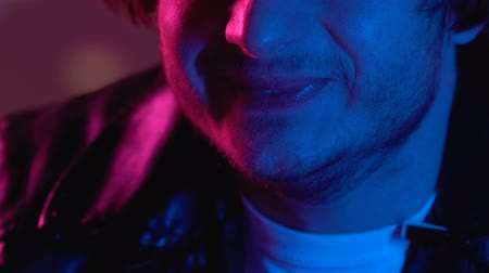 eufória : Weird man laughing in night club after smoking drugs, marijuana effect, close-up