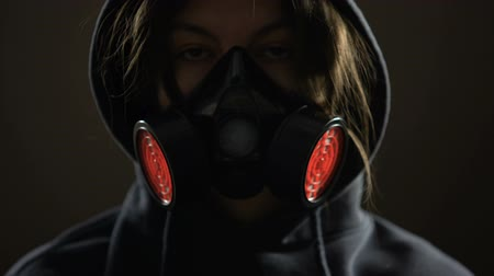 biological danger : Woman wearing respirator, flashing light alarm on background, protection concept