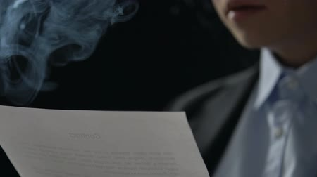 detective : Person nervously smoking reading contract terms, gangster fraud, close-up
