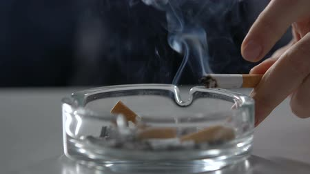 desempregado : Nervous person ashing cigarette into full of cigarette butt ashtray, addiction