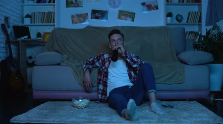 snoepen : Young student drinking beer and eating popcorn watching tv show, weekend leisure Stockvideo